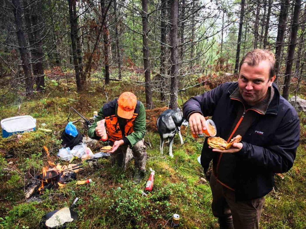 Mattias Brännholm äter hamburgare som Stig Engström har grillat. Jämthunden Saik åt flest burgare på den här lunchen.